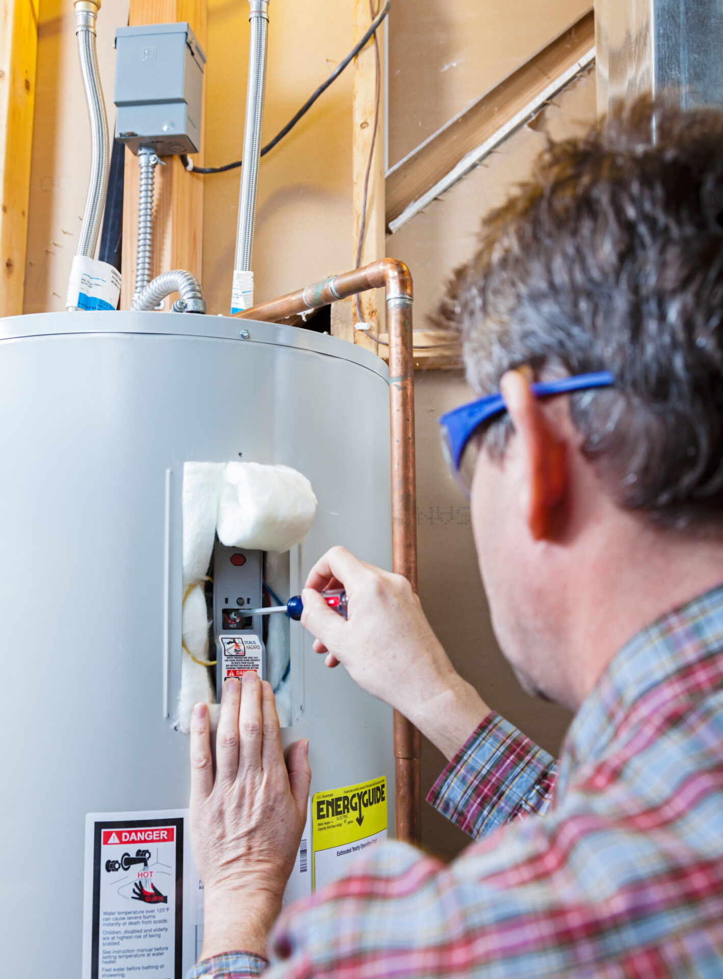 A technician is performing maintenance on a residential water heater